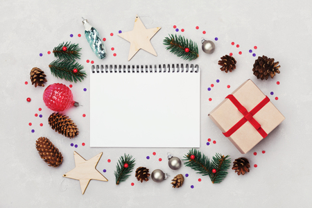 Christmas background of notebook, gift box, fir tree, conifer cone and holiday decorations on white table from above. Flat lay styling.