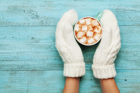 Photo for Woman hands in mittens hold cup of hot cocoa or chocolate with marshmallow on turquoise vintage table from above. Flat lay style. - Royalty Free Image