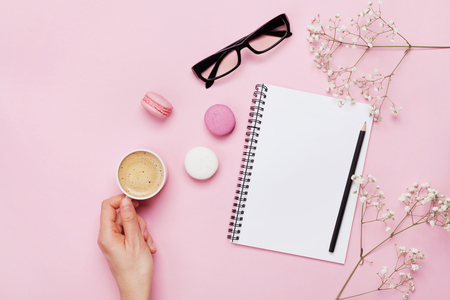 Woman hand hold cup of coffee, cake macaron, clean notebook, eyeglasses and flower on pink table from above. Female working desk. Cozy breakfast. Flat lay style.