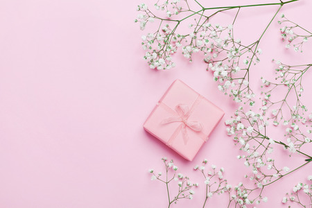 Photo pour Gift or present box and flower on pink table from above. Pastel color. Greeting card. Flat lay style. - image libre de droit