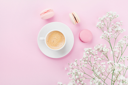 Photo pour Morning cup of coffee, cake macaron and flowers on pink table top view in flat lay style. Beautiful breakfast for woman. - image libre de droit