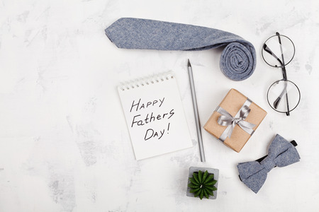 Photo pour Happy Fathers Day background with notebook, gift, glasses, necktie and bowtie on white table top view in flat lay style. - image libre de droit