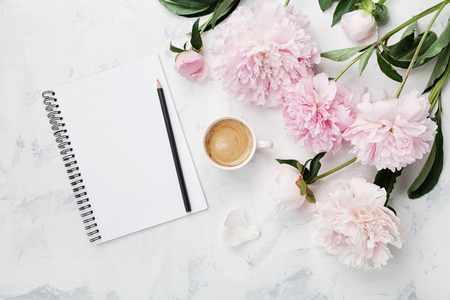 Photo pour Morning coffee mug for breakfast, empty notebook, pencil and pink peony flowers on white stone table top view in flat lay style. Woman working desk. - image libre de droit