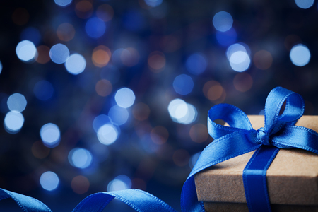 Foto de Christmas gift box or present with bow ribbon on magic blue bokeh background. Copy space for greeting text. - Imagen libre de derechos
