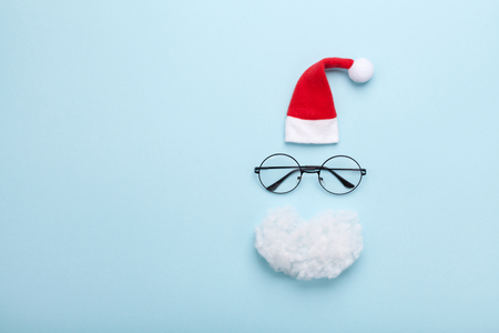Photo pour Creative Christmas composition. Greeting card, invitation. Santa hat, beard, and glasses on blue background top view. Flat lay. - image libre de droit