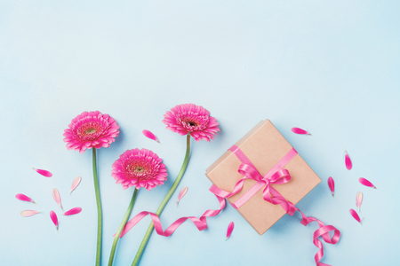 Foto de Spring composition with pink flowers and gift box on blue table top view. Greeting card for Birthday, Woman or Mothers Day. Flat lay. - Imagen libre de derechos