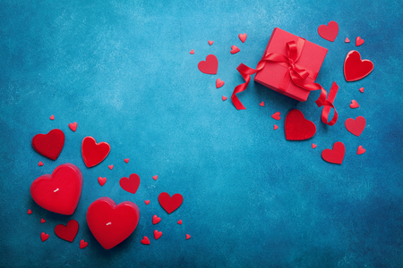 Foto de Holiday background with gift box and red hearts on blue table top view. Valentines day card. Flat lay. - Imagen libre de derechos
