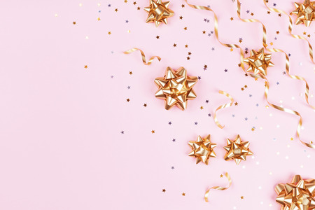 Photo for Fashion composition with golden bows, serpentine and star confetti on pink pastel table top view. Flat lay card for birthday, christmas or wedding. - Royalty Free Image