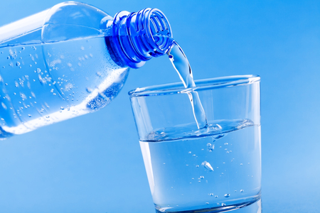 Photo pour Pouring drinking water from bottle into glass on blue background. - image libre de droit