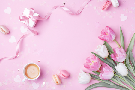 Photo for Morning cup of coffee, cake macaron, gift or present box and spring tulip flowers on pink background. Beautiful breakfast for Women day, Mother day. Flat lay. - Royalty Free Image