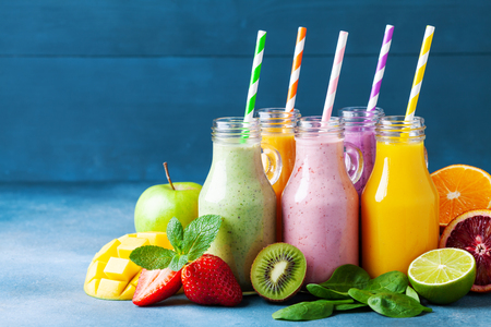 Foto de Summer colorful fruit smoothies in jars with ingredients. Healthy, detox and diet food concept. - Imagen libre de derechos