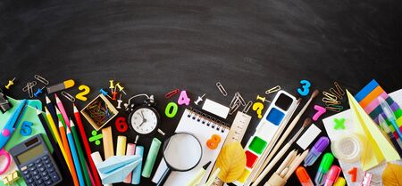 Photo pour Set of stationery, alarm clock and supplies on blackboard background. Back to school concept. Banner format. Top view. - image libre de droit