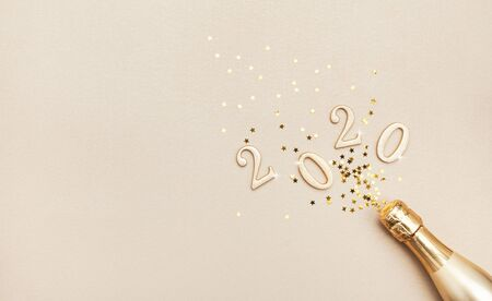 Photo for Creative Christmas and New Year composition with golden champagne bottle, confetti stars and 2020 numbers. Flat lay. - Royalty Free Image