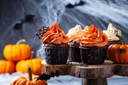 Photo for Halloween cupcakes and pumpkins on dark web background. Sweets for holiday party. - Royalty Free Image