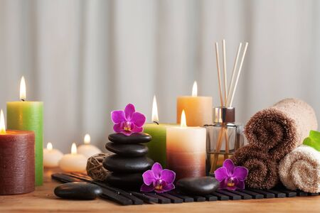 Foto de Aromatherapy, spa, beauty treatment and wellness background with massage stone, orchid flowers, towels and burning candles. - Imagen libre de derechos