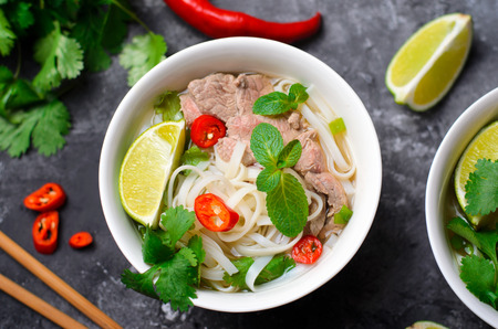 Photo pour Traditional Vietnamese Soup Pho Bo with Rice Noodles, Beef and Herbs on Dark Background, Asian Cuisine - image libre de droit