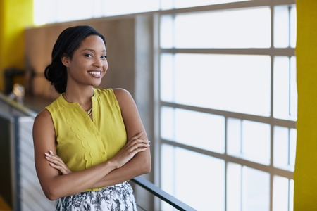 Friendly african american woman standing with arms crossed in a modern bright officeの写真素材