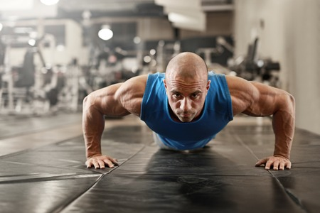 Foto de active and muscular man keeping fit by doing pushups on a floor mat - filtered image - Imagen libre de derechos