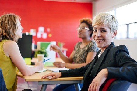 Photo pour Casual portrait of a business woman using technology in a bright and sunny startup with the team in the background - image libre de droit