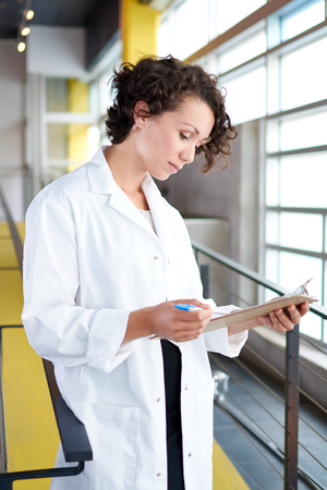 Friendly and attractive of a hispanic woman practitioner standing in a glass hall office of the clinic and examining documents