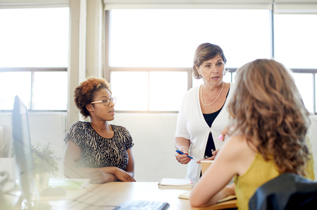 Foto per Candid picture of a female boss and business team collaborating. Filtered serie with light flares, bokeh, warm sunny tones. - Immagine Royalty Free