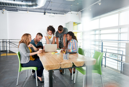 Photo for Group of young casual employees discussing a brainstorming project while researching ideas on a computer. - Royalty Free Image