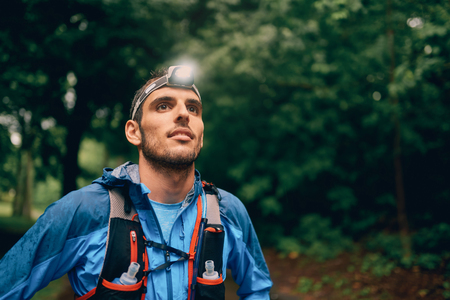Photo for Fit male jogger with a headlamp rests during training for cross country trail race in nature park. - Royalty Free Image