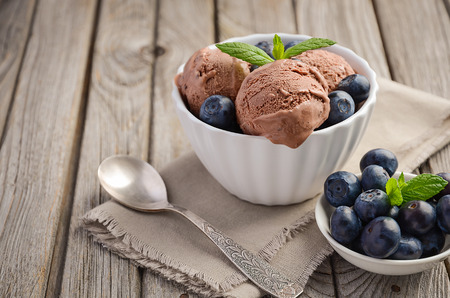 Chocolate ice cream with blueberries on rustic wooden background, selective focus, copy space