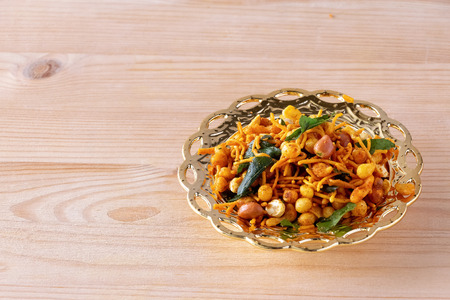 Photo pour South indian spicy crunchy mix Nimco or Namkeen with peanut, rice, curry leaves and spice golden bowl background isolated. - image libre de droit