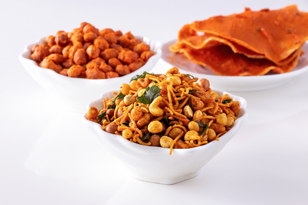 Photo pour Assortment salty crunchy indian mix Nimco or Namkeen, spicy coated peanut and pappadam white bowl wooden background. - image libre de droit