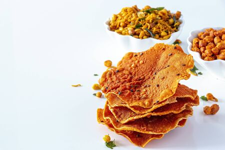Photo pour Pappadum South indian spicy crunchy mix Nimco or Namkeen with peanut, rice, curry leaves and spice white bowl background isolated. - image libre de droit