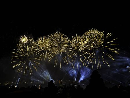 Photo for holiday and fun concept. Veriety colorful fireworks on the night sky background. People are watching to many flashes of yellow salute - Royalty Free Image