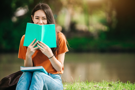 Foto de A young or teen asian girl student in university smiling and reading the book and look at the tablet or labtop computer in summer holiday. - Imagen libre de derechos
