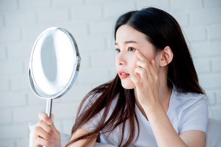 Photo pour Asian teenage woman  looking at mirror and squeeze acne problem on her face, skin care concept. - image libre de droit