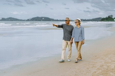Photo pour Asian senior couple or elderly people walking and siting at the beach on their weekend vacation holiday. Retirement vaction concept. - image libre de droit