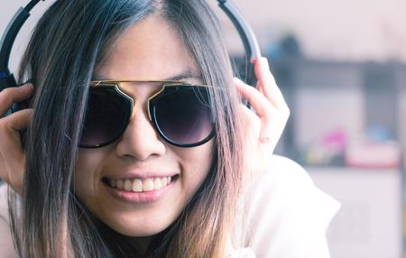Cute Asian girl is listening to pop dance music on headphone