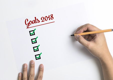 Hand writing down checklists for 2018 Goals on paper top view copy space