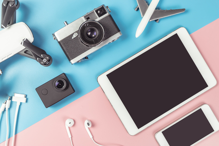 Travel gadgets flatlay on blue and pink background for travel concept