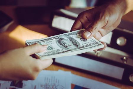 Photo pour Business man hands handing money over a business dealing - image libre de droit