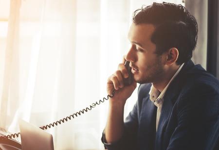 Photo pour Business man is making call in on Fax phone landline - image libre de droit