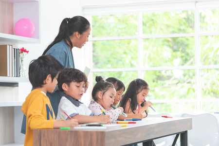 Foto de Asian Teacher is teaching children in kindergarten classroom - Imagen libre de derechos