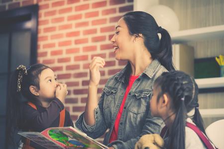 Foto de Teacher is reading story book to kindergarten students - Imagen libre de derechos