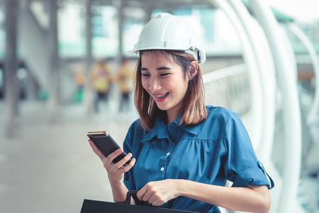 Foto de Young engineer woman is using mobile in a modern city - Imagen libre de derechos
