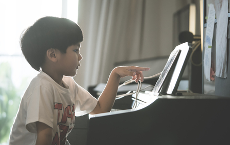 Photo pour Little Boy is playing with piano and Music Tablet at home - image libre de droit