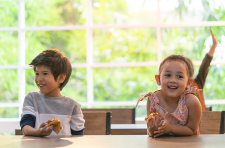 Photo for Kindergarten students hand up for more pizza - Royalty Free Image