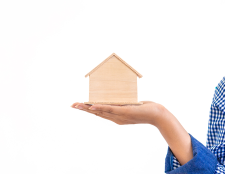 Photo pour Hand holding toy wooden house for real estate and housing business concept - image libre de droit