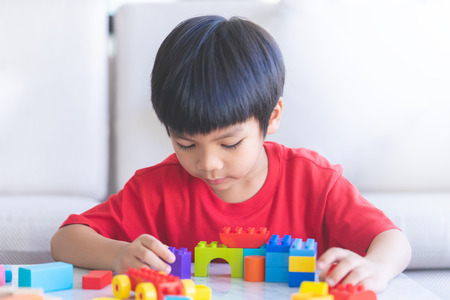 Photo pour boy playing Toy blocks in living room with hand up say hi - image libre de droit