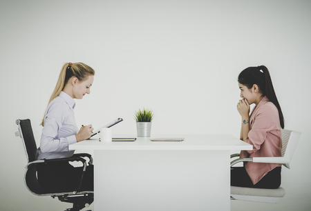 Boss and scared businesswoman serously talking in a job interview in an office