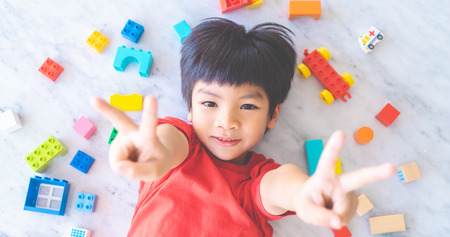 Photo pour Happy boy surrounded by colorful toy blocks top view V shape hand for victory - image libre de droit