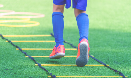 Photo pour Child feet with soccer boots training on agility speed ladder in soccer training. - image libre de droit